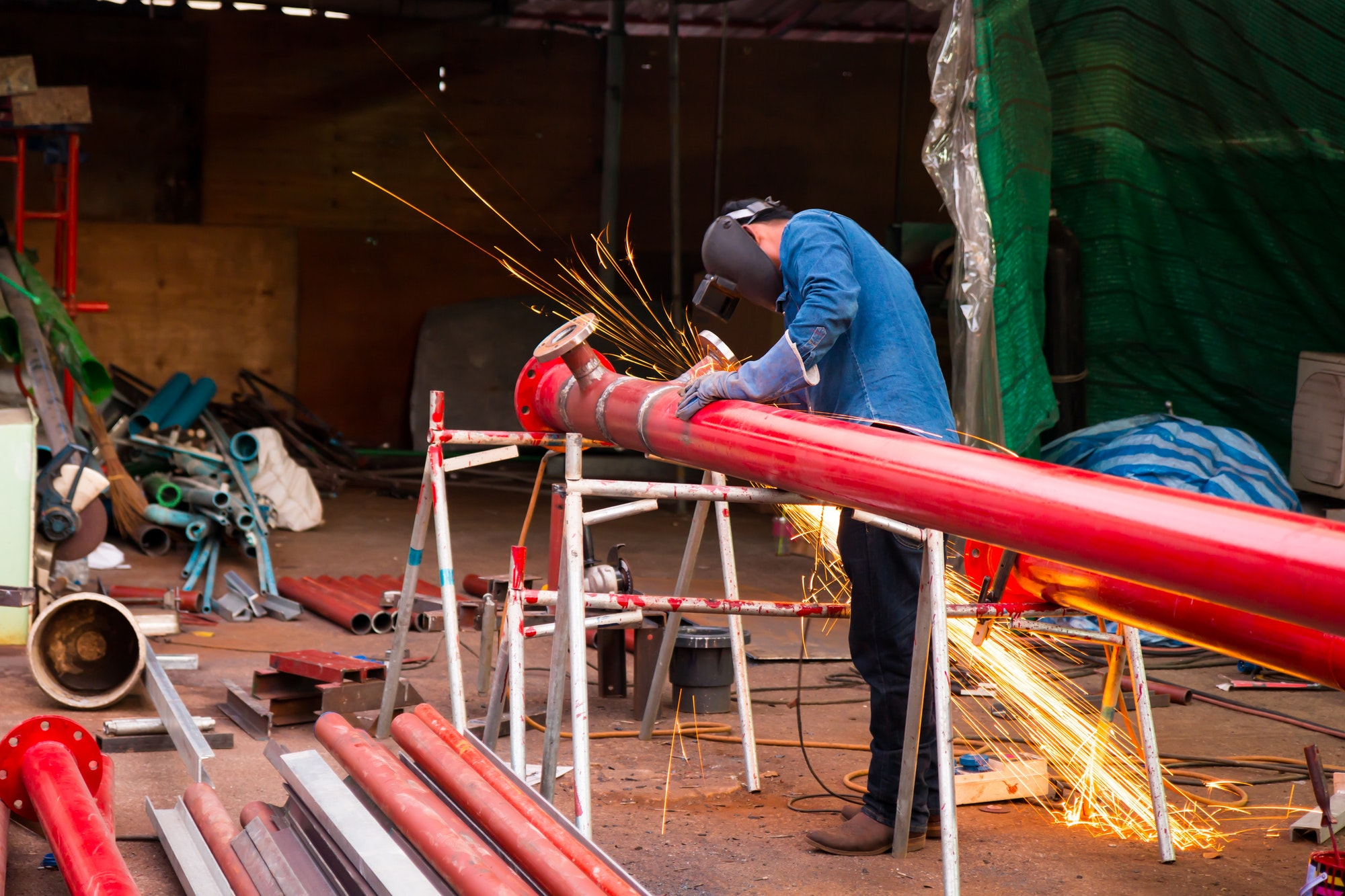 Worker cutting steel red pipe with acetylene welding cutting torch with industrial construction site